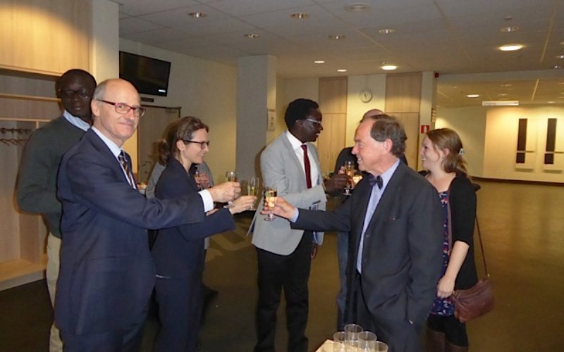 Prof. Robert Colebunders (Dr. George's supervisor on left) and Paul Fivat (former Swiss Diplomat) chat at a reception after successful PhD defence by Dr George in light grey jacket in back ground.